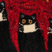 This is a photo of the hooked rug made by Laura Kenney. There are three black cats with yellow eyes, and each is wearing a white mask. The background is swirls of different reds, with bright yellow and orange stars. This is arguably the brightest image on the Halifax Examiner website.