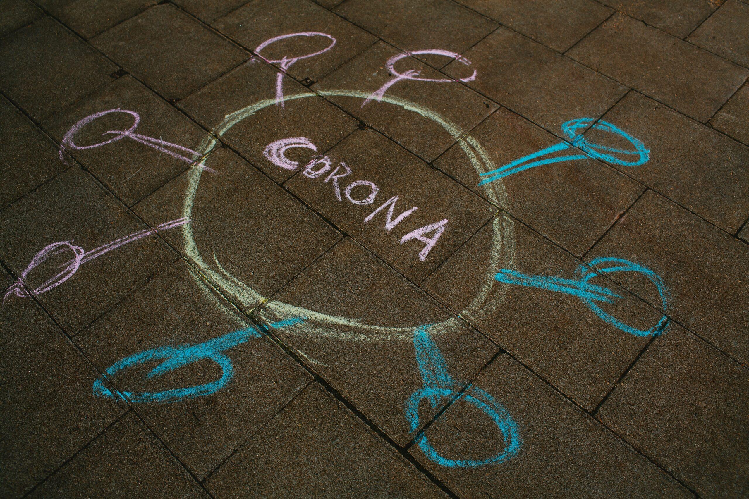 A photo of a chald cartoon of a coronavirus drawn on a concrete block sidewalk.