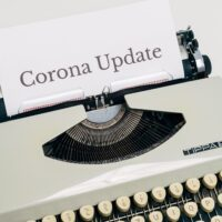 An old-style Tippa 5 typewriter from the 60s is shown with the words Corona Update printed in impossibly large text on the paper.