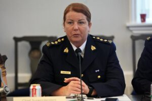 A photo of Halifax-district RCMP Chief Superintendent Janis Gray speaking at a meeting of the Halifax Board of Police Commissioners this past July. She is in her RCMP uniform and sitting at a desk in front of a microphone.