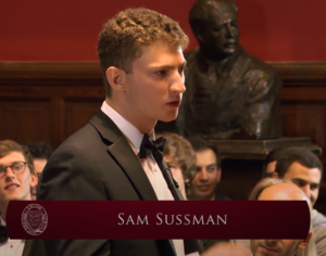 Young man in formalwear speaking. Banner says Sam Sussman