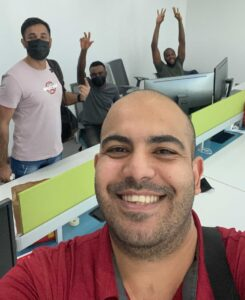 A smiling person with a bunch of happy-looking people at computers and wearing masks behind him