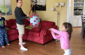 A photo of Olivia Healy as she hits a coronavirus piñata. Her dad, Jeff holds the piñata. Her brother Liam stands behind his dad, and the younger siblings Nestor and Charlotte are on the red couch. The kids are barefoot and wearing their pyjamas, Dad has dressed up in beige shorts, a black long-sleeved T shirt and white ankle socks.