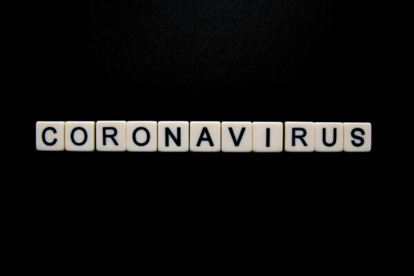 This is a photo of white letter tiles on a black backgound. The black text on the letters spells out coronavirus in capital letters.