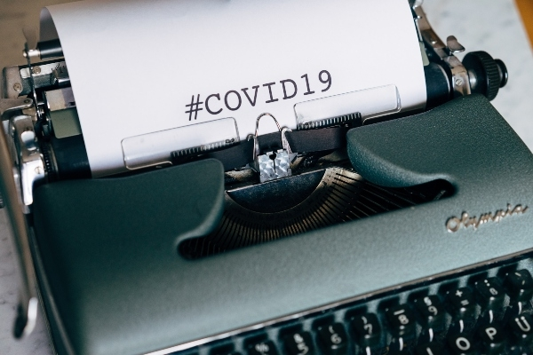 This is a close up of an old Olympia manual typewriter, blue grey in colour. There is a sheet of white paper in it, and the word COVID 19 has been typed in capital letters.