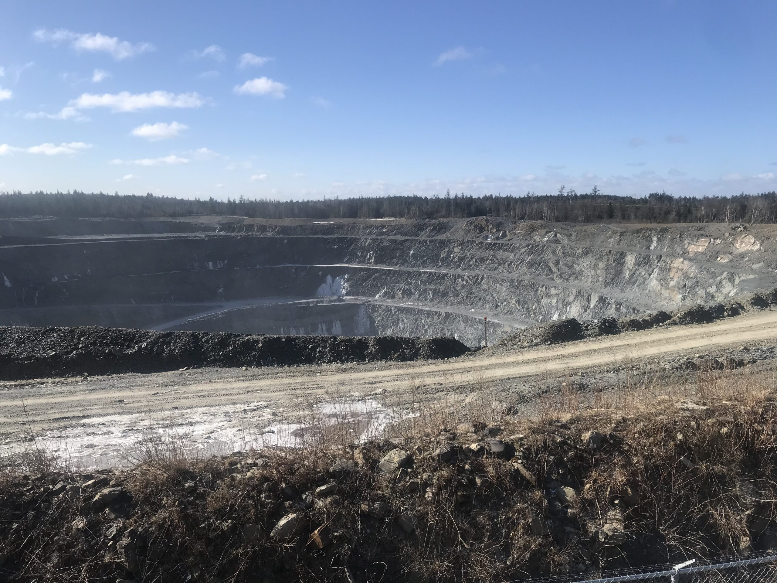 A photo of the Touquoy gold mine pit, taken from over a chain link fence on a sunny day. It's massive. In the far distance you can see a line of what's left of the trees. The pit is a big grey hole, with three connected ledges running around the inside of the pit.