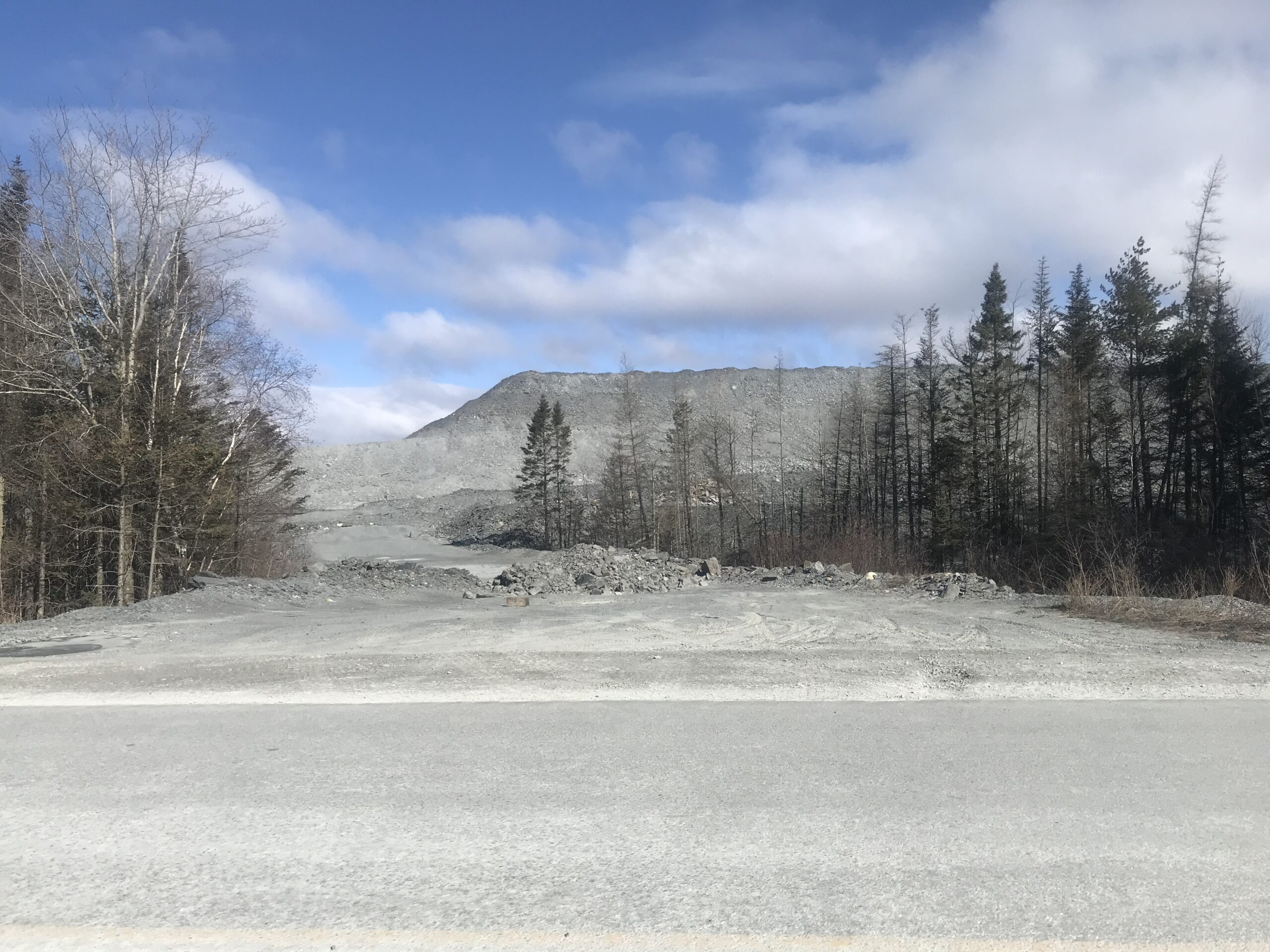 A photo of a grey dirt road in a mine site, with trees on both sides. The road leads to a massive pile of grey rock and dust.