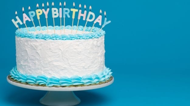 A white frosted birthday cake stands on a white cake pedastal against a blue background. On it is the phrase Happy Birthday spelled out in lit candles.