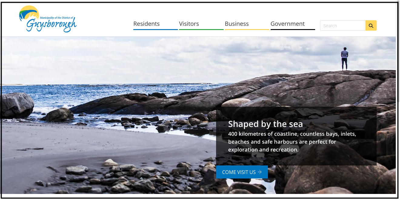 """A shot of the landing page of the Guysbourough District website. There is a photo of large rocks where they meet the ocean, and a small corner of beach. A woman is standing on top of the rocks, off in the distance, looking out to sea. The text reads """"Shaped by the sea. 400 kilometres of coastline, countless bays, inlets, beaches and safe harbours are perfect for exploration and recreation, unquote."""" Not for long, if some folks have their way."""