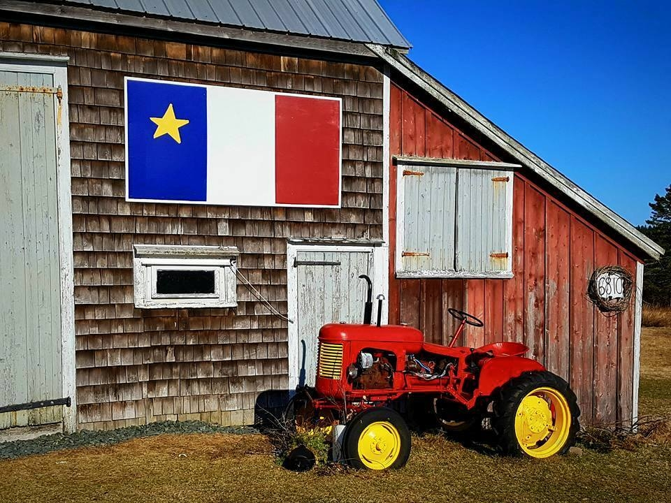This is a photo of a weathered barn with a bright painting of the Acadian flag mounted on it. Part of the barn is brown with a white door and trim, and there is a red painted addition to the barn. The Acadian flag has vertical bands of blue, white, and red, and there is a five pointed star in the top half of the blue band. In front of the barn is a bright red old style tractor with bright yellow wheels and thick black tires.