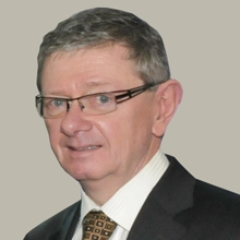 A photo of Ralston MacDonnell. He's an older white man, wearing a dark suit, white shirt and tie. He's looking sheepishly at the camera, as if he was just caught doing something sneaky.