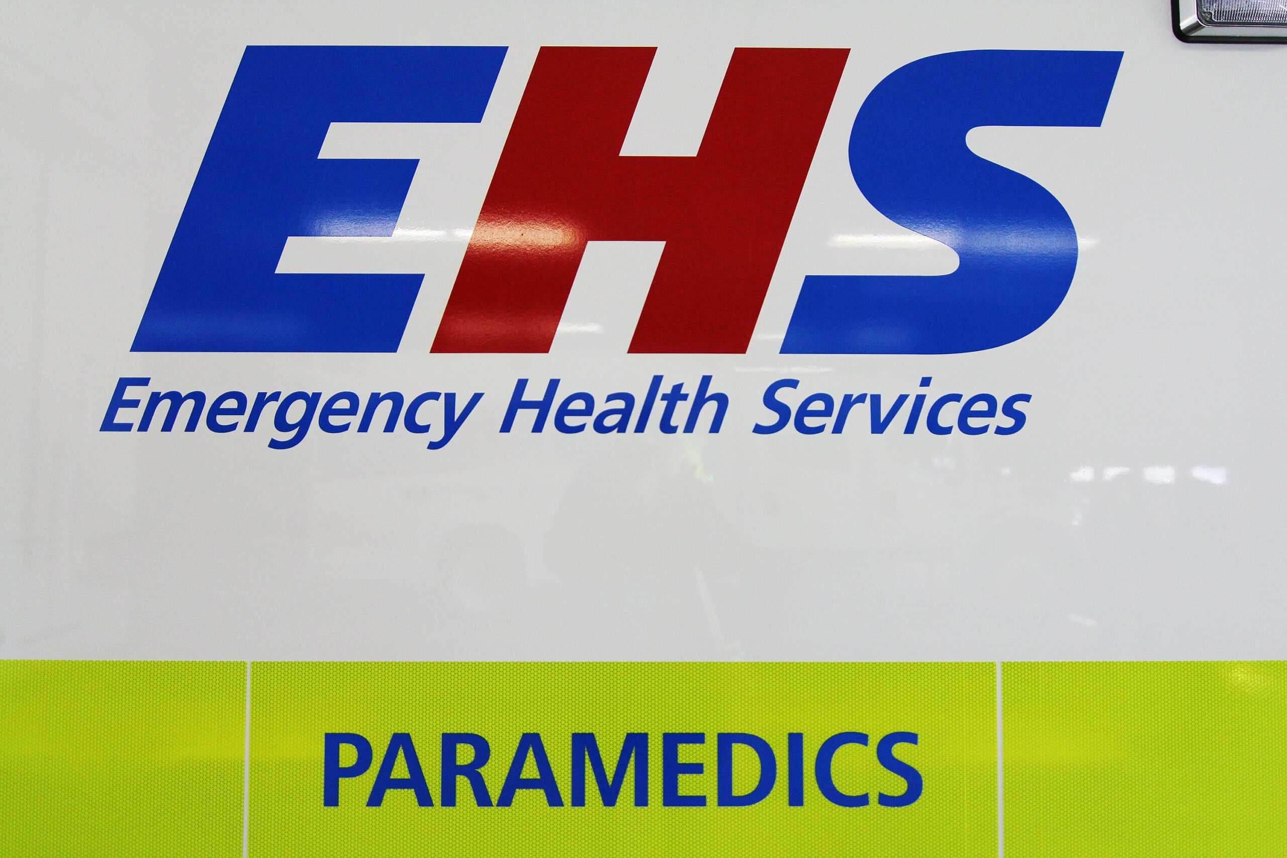 The Emergency Health Services (EHS) logo on a white ambulance. The E and S are royal blue, the S is red. Emergency Health Services is written below in italic font, and the word paramedics is below that in blue capital letters on a high visibility green stripe.