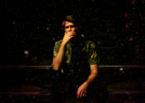 A photo of Adam Warren. He's wearing a patterned green shirt, and sitting pensively with his hand covering his mouth, in a very dark and moody room with specks floating in the air.