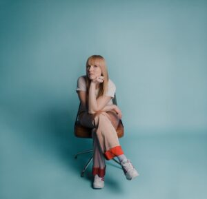 A photo of Breagh Isabel. She's sitting on a chair with her chin propped on her elbow, and her elbow propped on her crossed legs. She's wearing funky gold beige satin pants with a bright red cuff, her hair is a similar colour, and the background and floor is a lovely pale turquoise.