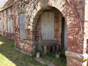 A photo showing the detail of the arched portico to the building. The bricks are weathered and xome have crumbled away. It looks like the red bricks may have been painted white at one time, but that has mostly worn off.