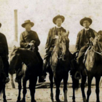 Sepia photo of six priests in cowboy style hats, clerical collars and long coats on horseback.