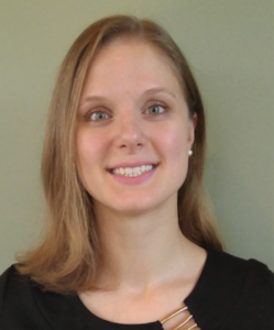 A photo of Dr. Meghan Pike. She's smiling at the camera, wearing a black top with metallic gold trim. She has blonde shoulder-length hair, and her green eyes perfectly match the colour of the wall behind her.