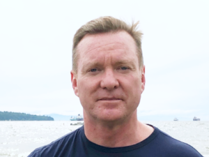 A photo of Dr. Edward Mills. It's a bright yet hazy summer day. He's looking directly at the camera, wearing a navy blue T shirt, and has a serious expression. In the background is what looks like Vancouver Harbour, with several container ships and fishing vessels off in the distance.