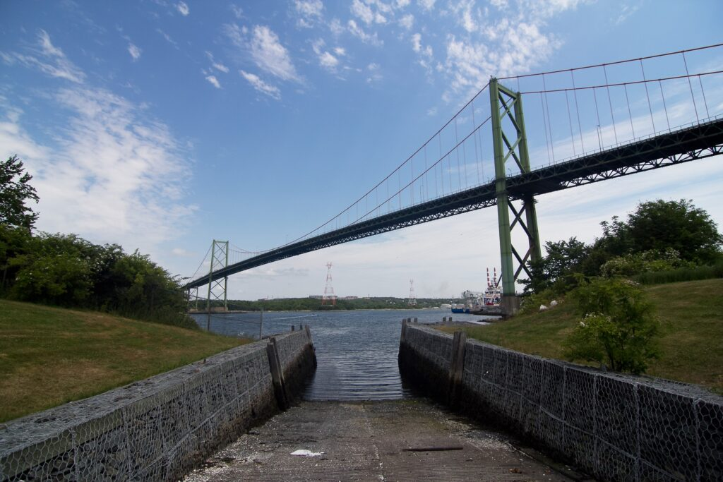 The A. Murray MacKay Bridge is seen from Africville on a sunny summer day in 2018. The photo is taken facing east, looking down the boat slip into the harbour, with the bridge spanning overhead. In the distance you can see the red and white stacks of Tufts Cove.