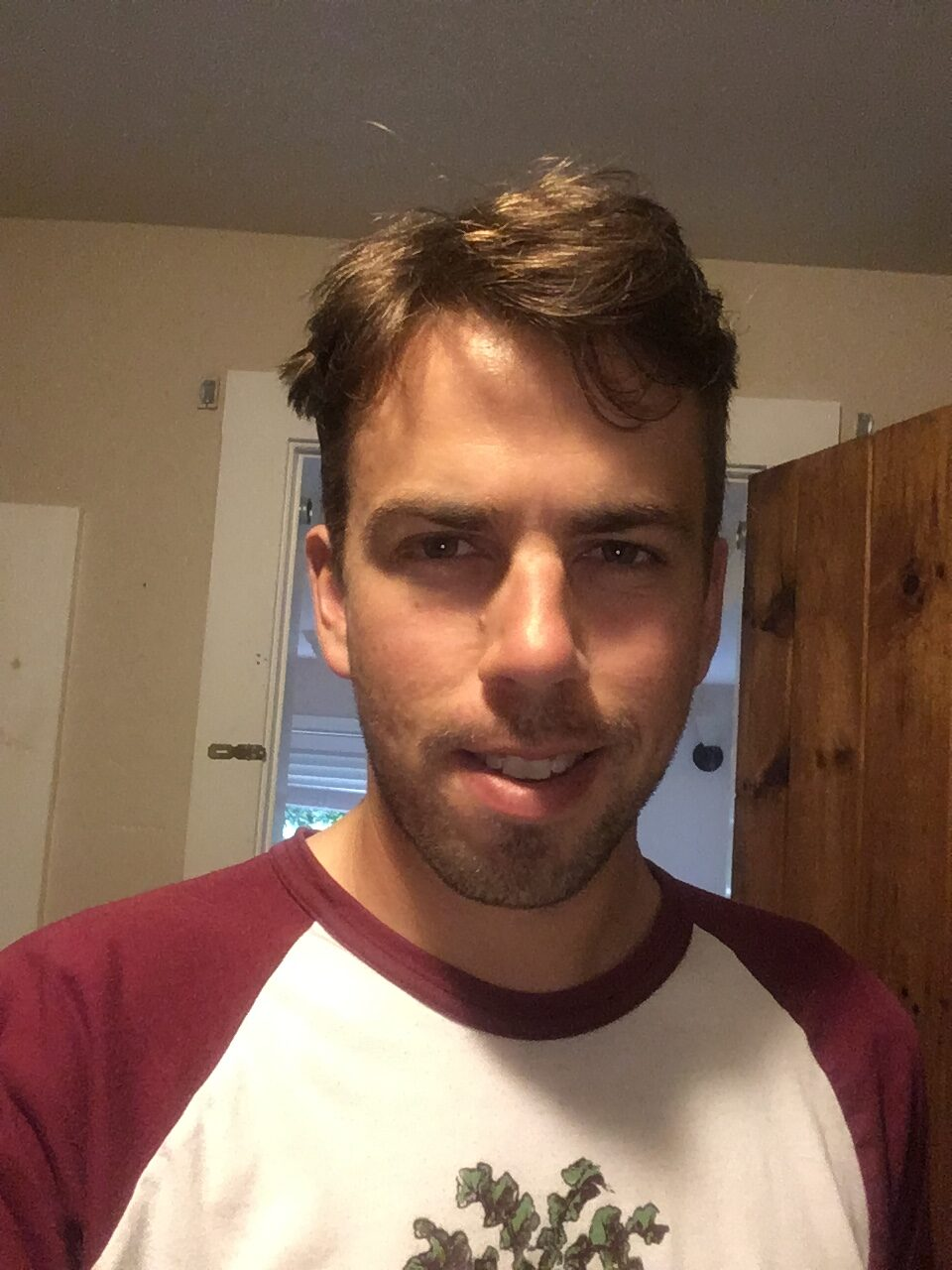 Ethan took a selfie. He's a good looking young man, smiling rather bashfully, wearing a white baseball Tshirt with burgundy raglan sleeves, and what looks like an illustration of thistles on it. His brown hair is newly cut, and he needs a shave.