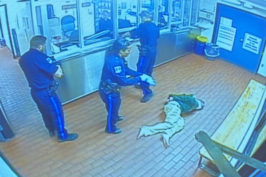 A screenshot of grainy surveillance video shows three uniformed police officers and a man laying on a brown brick floor. On the right there's a bench where prisoners would typically sit while getting booked. On the left there's a plexiglas barrier between the officers and a booking officer in an office.