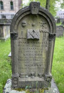 A headstone on a grave from 1821. It has masonic elements carved on it, an arched top, and and two Corinthian columns on each side.