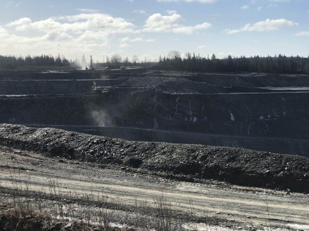 A photo of the Touquoy open pit gold mine. At the horizon about a kilometre away you can see aline of evergreen and hardwood trees silhouetted against a bright blue sky with a few puffy clouds. closer, you can see some equipment that's rasiing clouds of duxt. In the middle of the photo is the awesomely deep pit in the ground. In the foreground is a dry gravel road with tire tracks, and the guts of the earth are piled up in a bank between the road and the deep deep pit.