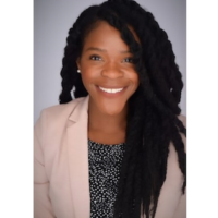 A studio photo of Doctor Tiffany Richards. She is smiling directly at the camera, and is wearing a blush coloured blazer and black and white dotted top. Her hair is long and dark, styled in a multitude of thick braids.