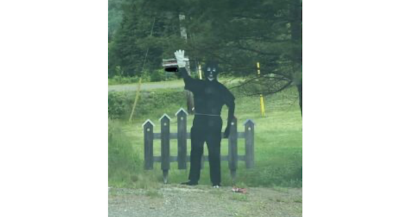 A photo of a blackface effigy erected in Parrsborough. It's completely black except for cartoony white features and one white glove on its right hand. Behind it is a cartoony black picket fence and a green lawn.