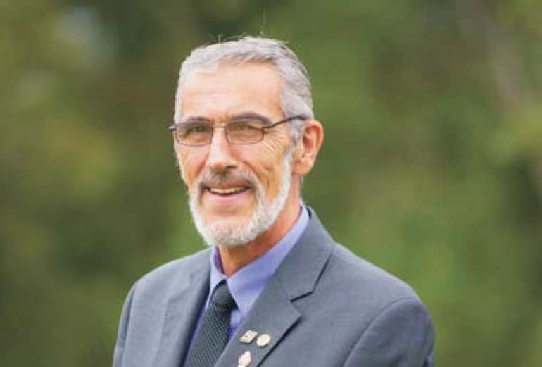 A photo of Vernon Pitt, taken outside on an overcast summer day. There is a blurred background of green trees. He is smiling with a crafty, squinty smile at the camera. He's wearing a grey suit with lavender shirt and grey tie. He has three lapel pins. He's got salt and pepper hair and a grey goatee, and wire rimmed glasses.