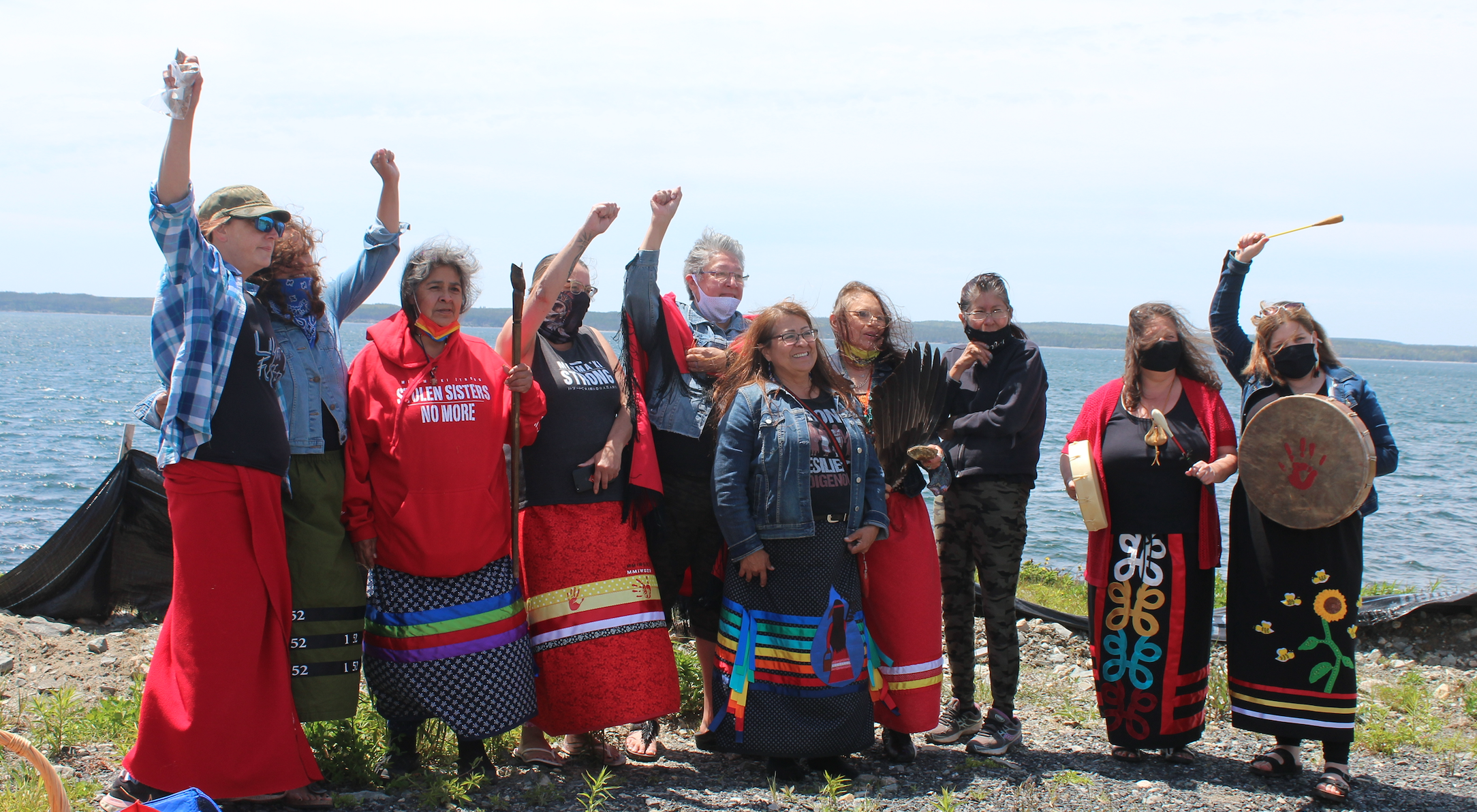 Ten Mi'kmaw women protest at Goldboro. It's a beautiful sunny day, and they are standing shoulder to shoulder with the ocean in the background. They are wearing brightly coloured ribbon skirts, and two of them have drums. Many of them have their fists raised.