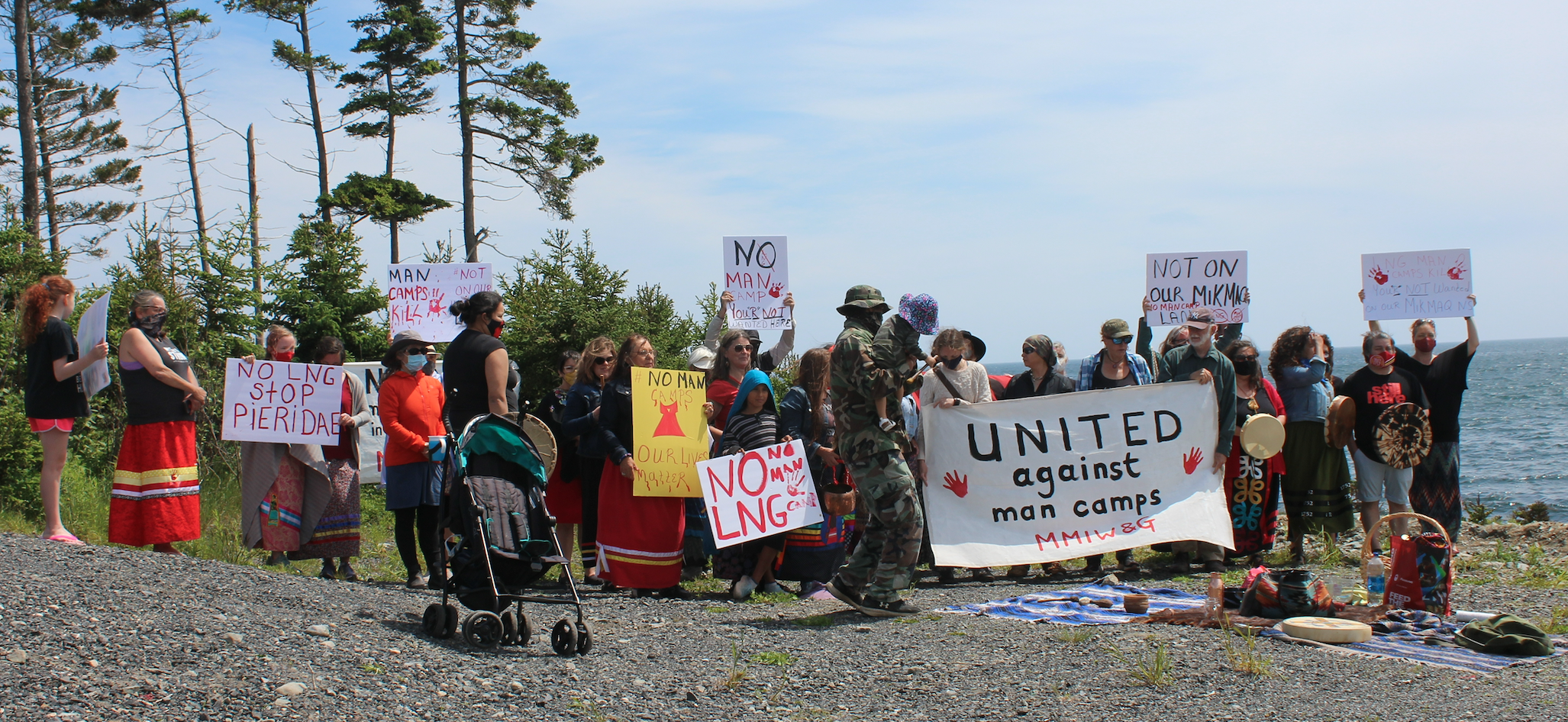 A sizable group of approximately 25 people at a protest, with the ocean in the background. Some are holding home made signs, many are wearing ribbon skirts, and there is a picnic blanket in the foreground with drums and other objects on it.