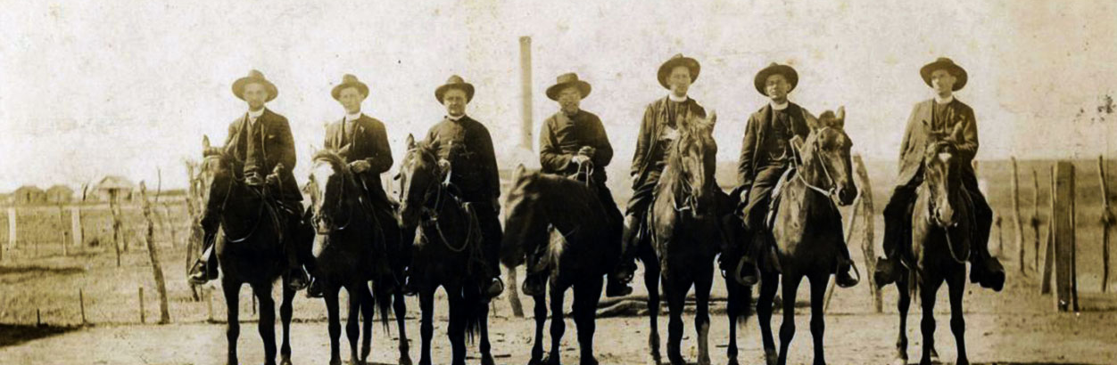 Sepia photo of five men in cowboy style hats on horsebakc.