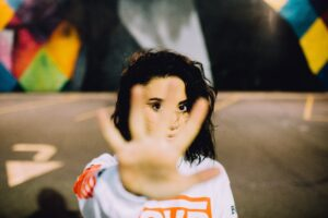 """A young woman holds up the palm of her hand to the camera as if to say """"STOP""""."""