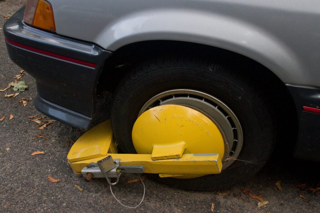 A yellow, metal boot, with a padlock is seen on the front driver's side wheel of an older model grey vehicle with dark grey trim and a red stripe.