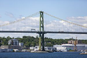 The Angus L. Macdonald Bridge on a sunny day in June 2021. You can see the irving Shipyard, and the trees and buildings of the North End.