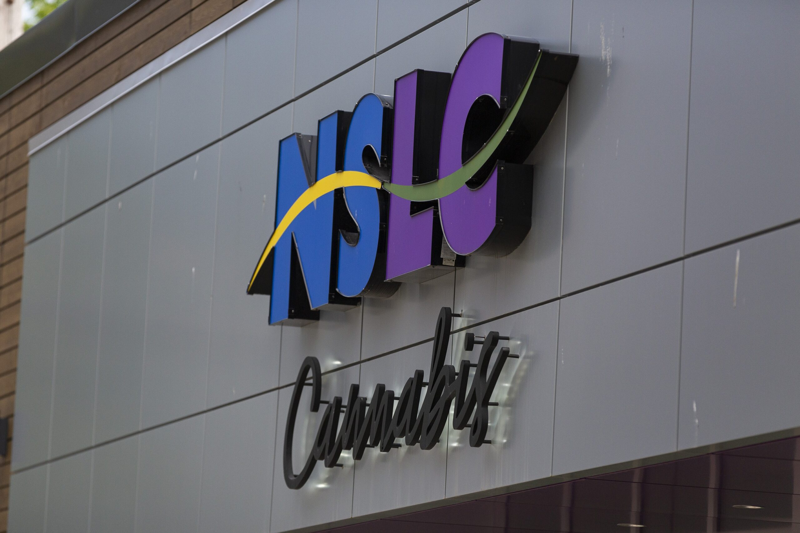 The sign on the outside of the NSLC Cannabis store on Clyde Street in Halifax in June 2021. The NSLC Logo is capital letters in blue and purple, with a yellow and green wave running over the centre. Below that, Cannabis is in black cursive text, set out from the building's surface.