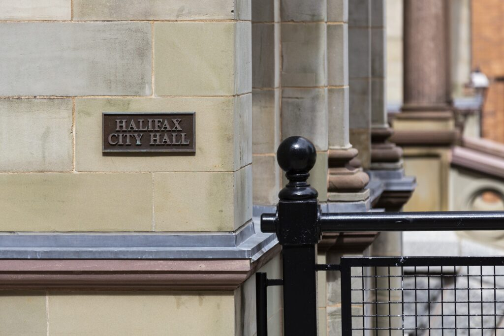 A photo of the bronze sign reading Halifax City Hall, set into the stone wall on the corner of the building. Taken in June 2021