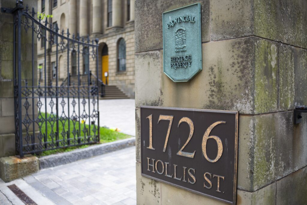 The open wrought iron entrance gate to the courtyard of Province House in June 2021. On the stone wall is a bronze plaque reading 1726 Hollis St, and above that a copper plaque, completely green with patina, designating the building a provincial heritage property.