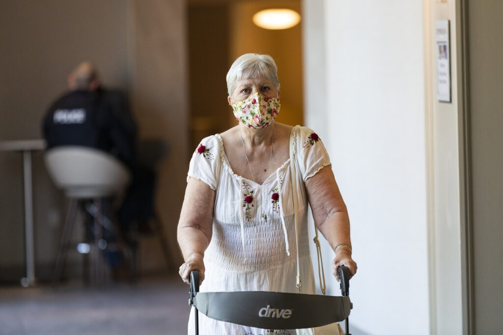 A woman uses a walker to walk down a hallway at a hotel, arriving for a Police Review Board hearing. She's wearing a white dress and a flowery cloth mask.