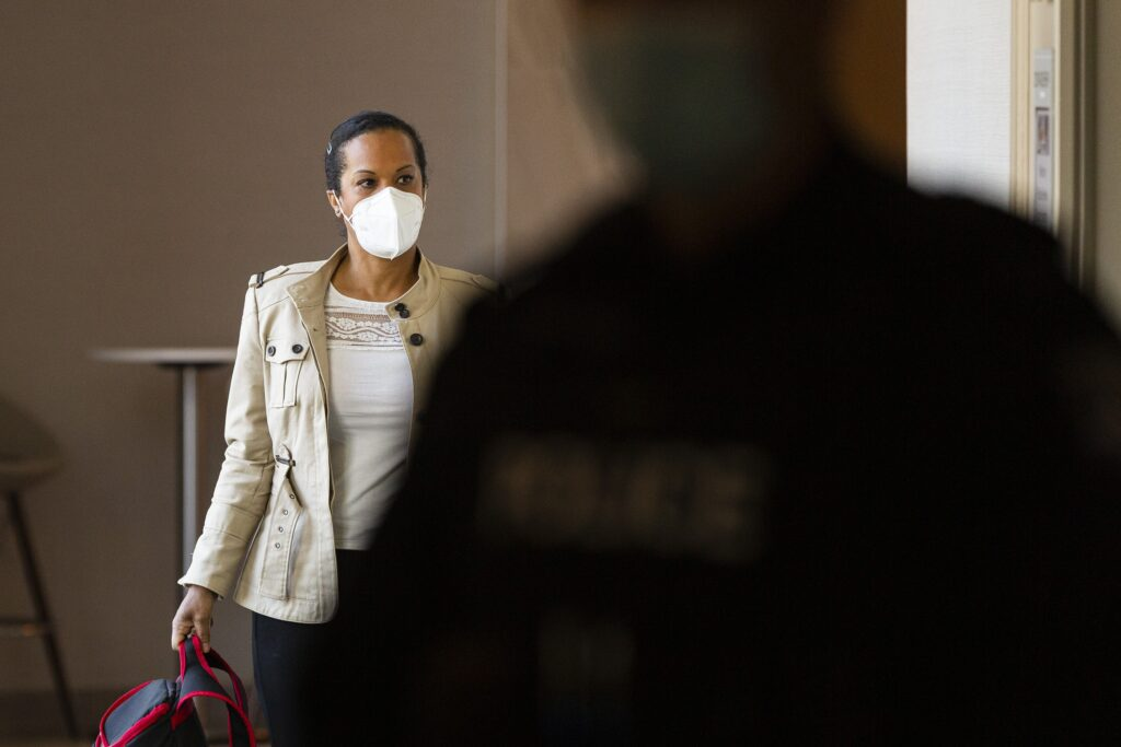 A woman wearing a white mask and a brown jacket, holding a backpack, walks down a hotel hallway, looking to her left. In the foreground, a blurry police officer wearing a mask crosses the scene.