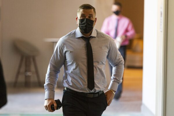 A man wearing white and black polka dot shirt and a black tie and a black mask walks down a hotel hallway.