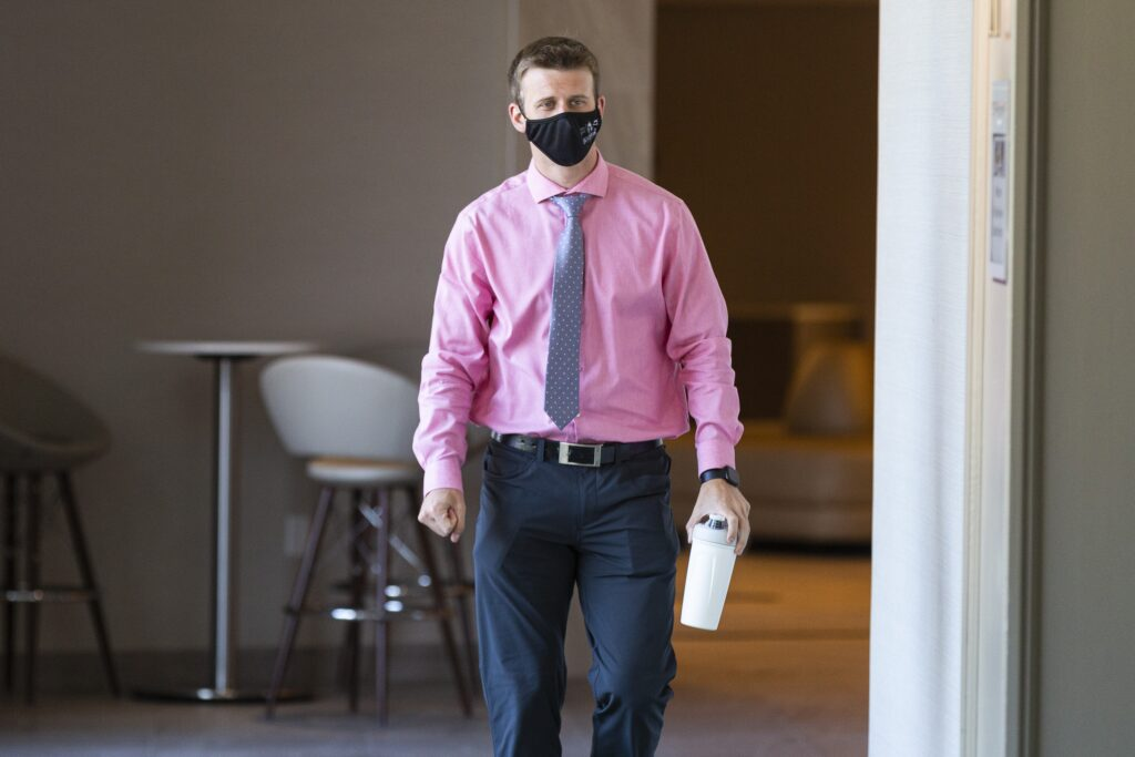 A man wearing a pink shirt, grey tie, and black mask walks down a hotel hallway carrying a white water bottle in his left hand, and clenching his right fist.