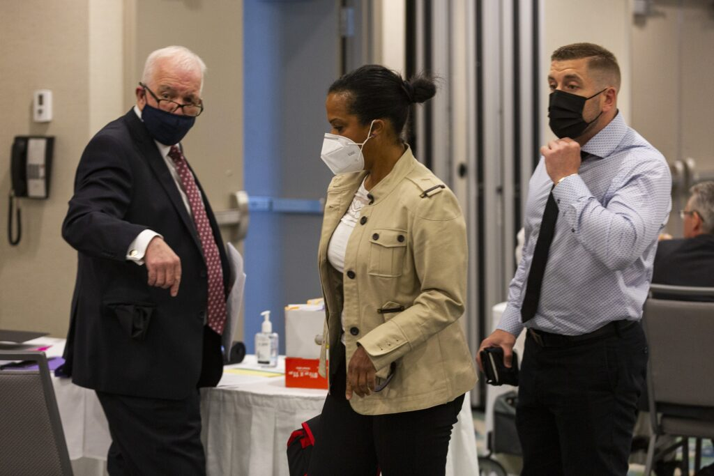 A man in a suit wearing a dark mask, a woman in a brown jacket wearing a white mask, and a man in a shirt and black tie and a black mask are seen in a conference room.