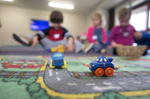 Three children play with toy cars on a carpet printed with a road.