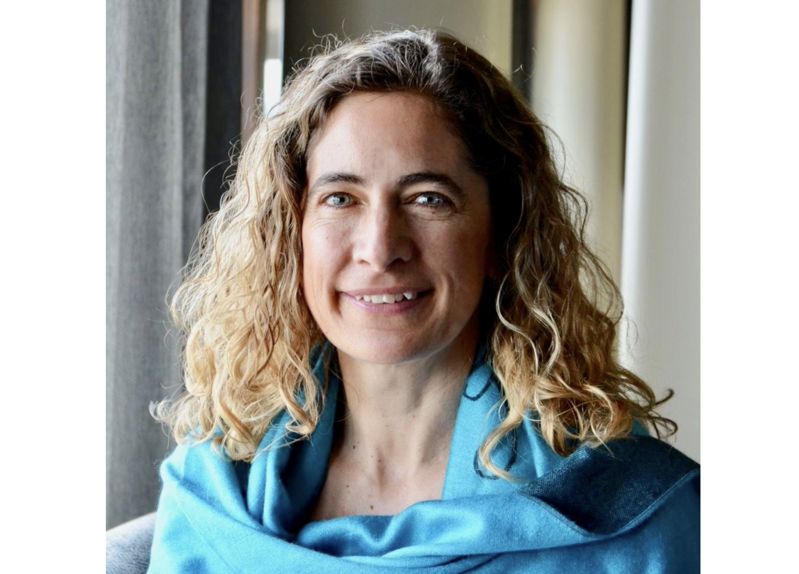 Headshot of woman with shoulder-length hair in a blue sweater, with a curtained background.