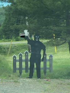 A photo of a blackface effigy erected in Parrsborough. It's completely black except for cartoony white features and one white glove on its raised right hand. Behind it is a cartoony black picket fence and a green lawn.