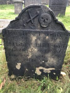 A very weathered headstone, with a section on top in which you can see a carved skull and a pair of blacksmith's tongs.