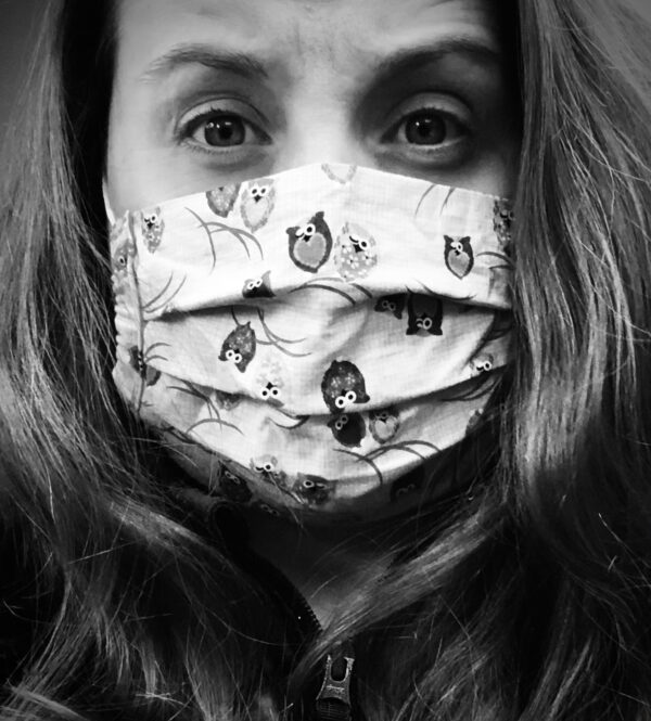 A bl;ack and white photo of Jennifer Mont. her dark hair frames her face, which has a worried expression. she's wearing a fabric mask with cartoon owls printed on it.