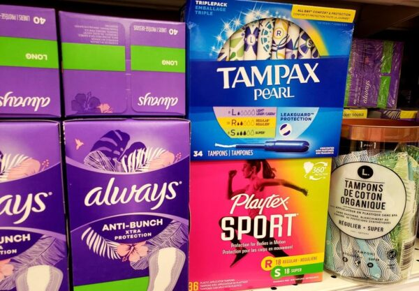 A photo of a selection of menstrual products on a shelf in a store.